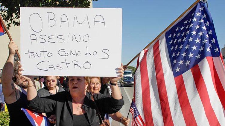 """(Une Américaine porte un panneau """"Obama est un meurtrier comme les Castro"""" © Reuters-Javier Galeano)"""