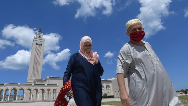 Un couple de Tunisiens portant des masques à la sortie de la prière du vendredi, le 5 juin 2020 à Carthage. (FETHI BELAID / AFP)
