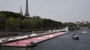 Une piste flottante d'athlétisme, ici en cours d'assemblage, posée sur la Seine, pour promouvoir vendredi 23 juin et samedi 24 juin, la candidature de Paris aux jeux Olympiques de 2014. (JOEL SAGET / AFP)