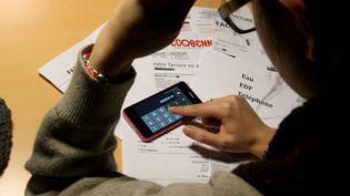 Une femme calcule le montant de ses factures. Photo d'illustration. (PIERRE HECKLER / MAXPPP)