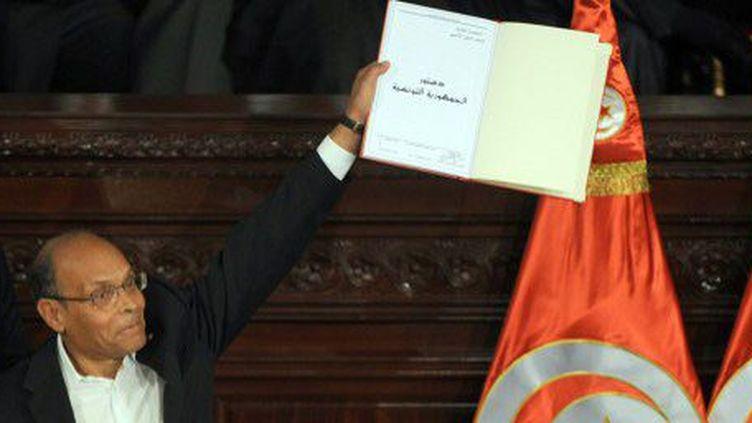 Le président tunisien, Moncef Marzouki, brandit la nouvelle Constitution lors d'une cérémonie à l'Assemblée nationale après l'adoption du texte, le 27 janvier 2014. (AFP - Fethi Belaid)