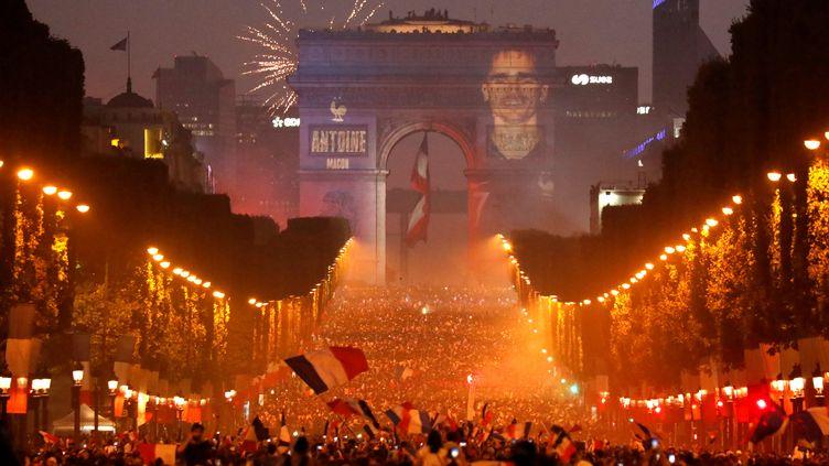 Tel celui de Zidane vingt ans plus tôt, le visage d'Antoine Griezmann est apparu sur l'arc de Triomphe face à des Parisiens en liesse dimanche soir. (CHARLES PLATIAU / REUTERS)