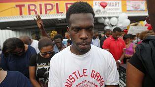 Des gens se recueillent à Bâton-Rouge (Etats-Unis), le 6 juillet 2016, après la mort d'Alton Sterling, un Noir tué lors d'une altercation avec la police. (GERALD HERBERT / AP / SIPA)