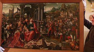 """Décrochage du tableau flamand """"L'Adoration des Mages"""" de l'église de Cudot dans l'Yonne, prêté pour quelques mois au musée du Louvre.  (Culturebox - capture d'écran)"""