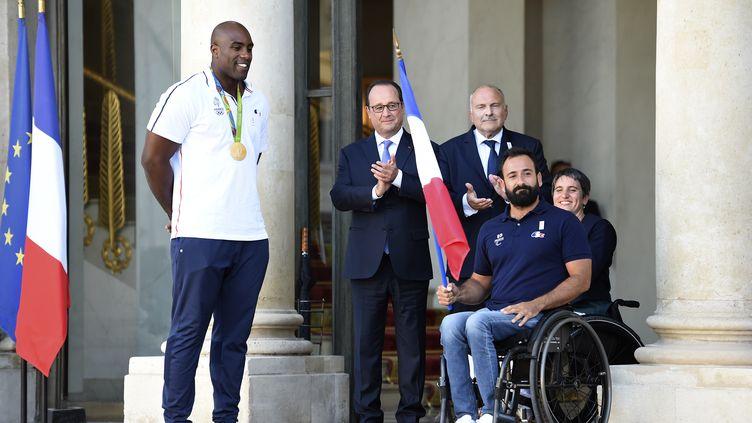 Michaël Jérémiasz avec Teddy Riner et François Hollande lors de la transmission du drapeau pour les Jeux Paralympiques de Rio.  (STEPHANE DE SAKUTIN / AFP)