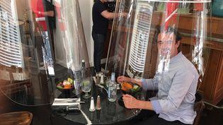 Christophe Gernigon présente son Plex'eat dans un restaurant parisien. Une cloche en plexiglas qui permet de protéger les clients contre le coronavirus. (BENJAMIN MATHIEU / FRANCEINFO / RADIO FRANCE)