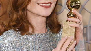 Isabelle Huppertbrandit sa statuelle de la meilleure actrice lors de la cérémoniedes Golden Globes, le 8 janvier 2017, à Beverly Hills, en Californie (Etats-Unis). (JOSHUA BLANCHARD / GETTY IMAGES NORTH AMERICA / AFP)