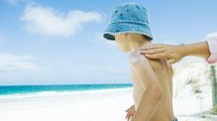 Un enfant est protégé des rayons UV du soleil par une crème de protection. (MAXPPP)