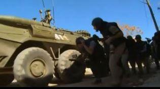 Capture d'écran montrant des journalistes étrangers qui se protègent des bombardements derrièreun blindérusse àà Kinsibba, dans la région de Lattaquié (Syrie), le 1er mars (APTN)