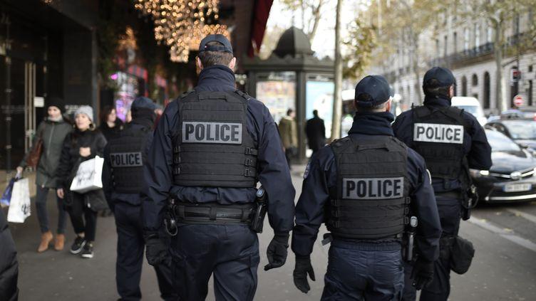 Quatre policiers de dos, le 30 novembre 2017, à Paris. (STEPHANE DE SAKUTIN / AFP)