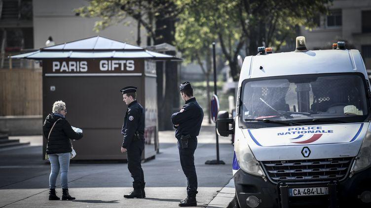 Des policiers contrôlent l'attestation de déplacement d'une passante à Paris, le 28 mars 2020. (STEPHANE DE SAKUTIN / AFP)