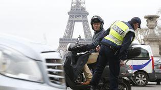 Un policier contrôle la plaque d'immatriculation d'un scooter, le 17 mars 2014 à Paris alors qu'une mesure de circulation alternée a été prise. (FRANCOIS GUILLOT / AFP)