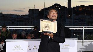 Hirokazu Kore-Eda, qui remporte la Palme d'or, pose avec son trophée le 19 mai 2018 à Cannes. (ANNE-CHRISTINE POUJOULAT / AFP)