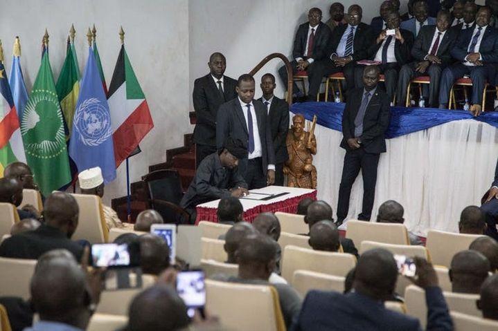 """Sidiki Abbas, leader du groupe armé 3R, signe l'""""accord de Khartoum"""" à Bangui, le 6février 2019.  (FLORENT VERGNES/AFP)"""
