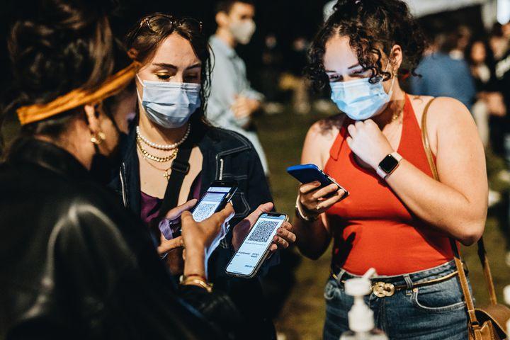 """Deux clientes présentent leur QR code généré pour le pass sanitaire, avant de pouvoir retirer leur masque, seulement """"recommandé"""" à l'intérieur. (PIERRE MOREL / FRANCEINFO)"""