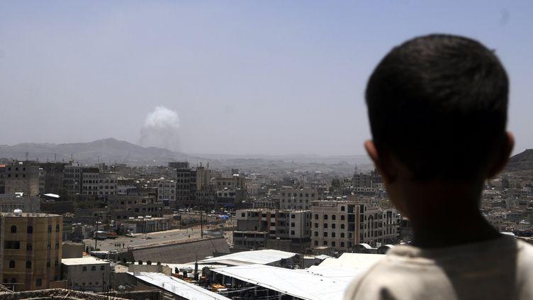 Un garçon regarde des bombardements de la coalition arabe sur Sanaa, la capitale yéménite, le 21 avril 2015. (HANI ALI / NURPHOTO / AFP)