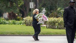 Une employée du cimetière Hollywood Forever Cemetery apporte des fleurs au cours des funérailles deL'Wren Scott, la compagne de Mick Jagger, le 25 mars 2014  (JOE KLAMAR / AFP)
