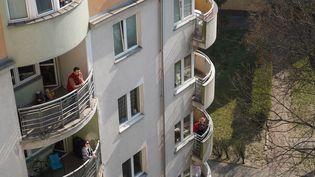 Des habitants confinés profitent du soleil à leur balcon, le 28 mars 2020, à Varsovie. (JANEK SKARZYNSKI / AFP)