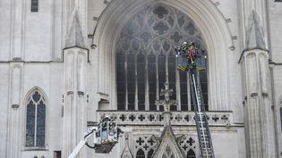 Des policiers tentent d'éteindre l'incendie qui ravage la cathédraleSaint-Pierre-et-Saint-Paul de Nantes (Loire-Atlantique), le 18 juillet 2020. (SEBASTIEN SALOM-GOMIS / AFP)