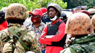 Bobi Wine, de son vrai nomRobert Kyagulanyi, est bloqué par des policiers, puis arrêté à Kalangala en Ouganda le 30 décembre 2020. Désormais, il porte un gilet pare-balles et un casque lors de sa tournée électorale. (Reuters/Stringer)