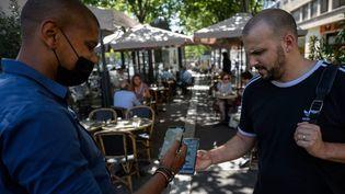 Un client montre son pass sanitaire à la terrasse d'un restaurant à Marseille (Bouches-du-Rhône), le 9 août 2021. (CHRISTOPHE SIMON / AFP)