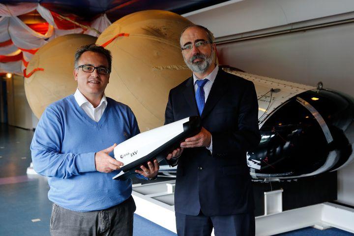 Le chef de la missionIXV,Giorgio Tumino (à gauche), et le manager Jose Maria Gallego prennent la pose devant une réplique de l'avion spatiale européenIXV, le 9 septembre 2014 àNoordwijk Aan Zee (Pays-Bas). (BAS CZERWINSKI / ANP / AFP)