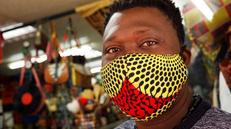 Un travailleur porte un masque dans un magasin de tissus à Cape Town en Afrique du Sud, le 15 mai 2020. (MIKE HUTCHINGS / X00388)