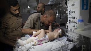 Mohammad Al-Hadidi réconforte son bébé Omar, blessé par une frappe israélienne, le 16 mai 2021 dans un hôpital de Gaza. (ALI JADALLAH / ANADOLU AGENCY / AFP)