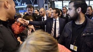 Emmanuel Macron et Alexandre Benalla (à droite), responsable de la sécurité du candidat pendant sa campagne, lors d'une visite au Salon de l'agriculture, le 1er mars 2017 à Paris. (LIONEL BONAVENTURE / AFP)