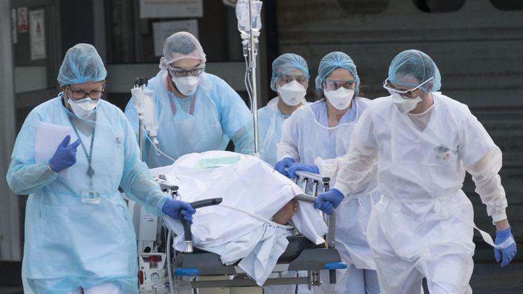 Une équipe médicale de l'hôpital de Mulhouse (Haut-Rhin) amène un patient souffrant du Covid-19 à un hélicoptère pour qu'il soit pris en charge dans un autre établissement, le 17 mars 2020. (SEBASTIEN BOZON / AFP)