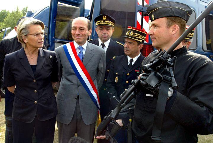 Un adjudant de gendarmerie (à droite) présente un fusil Tikka à la ministre de la Défense Michèle Alliot-Marie, le 21 juin 2005, au fort de Charenton (Val-de-Marne). (PASCAL PAVANI / AFP)