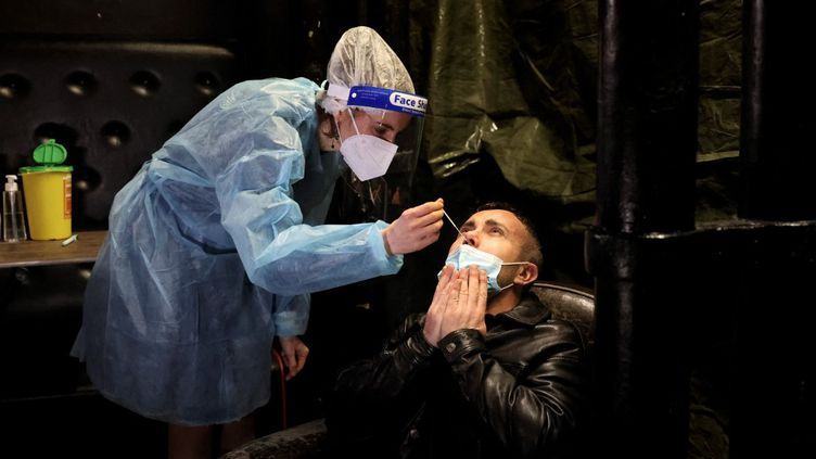 Un homme subit un prélèvement nasal, à Paris, le 5 février 2021. (THOMAS COEX / AFP)
