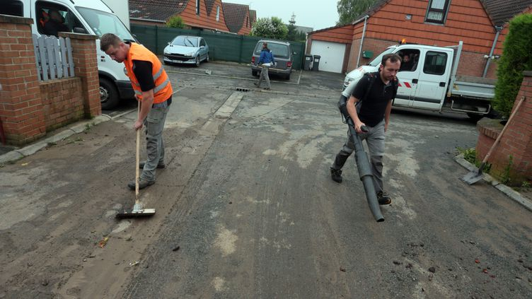 Les habitants de la commune de Haisnes (Pas-de-Calais) nettoient une rue, le 8 juin 2016. (MAXPPP)