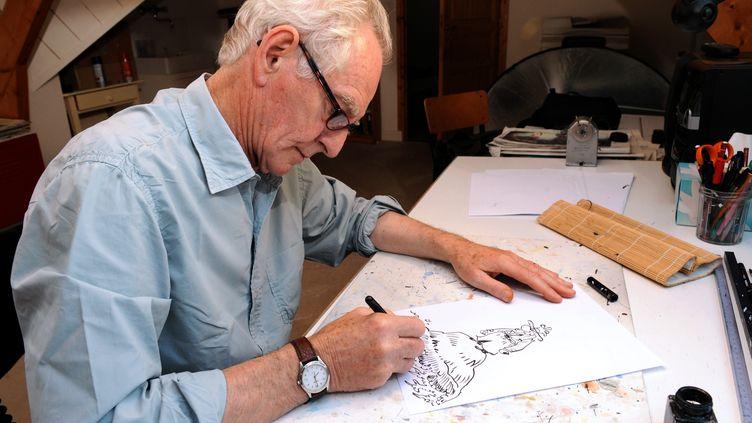 Le dessinateur René Pétillon dessine son personnage Jack Palmer, le 3 septembre 2013 à Nevez (Finistère). (FRED TANNEAU / AFP)