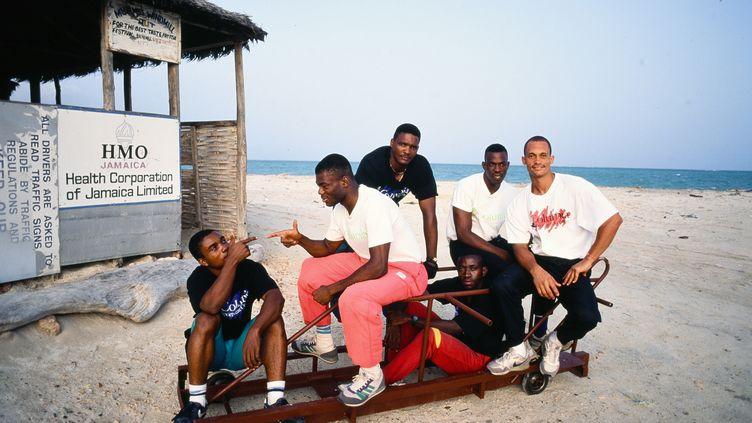L'équipe jamaicaine de bobsleigh aux Jeux olympiques de 1988 de Calgary (Canada), sur la plage de Kingston (Jamaïque), le 2 mai 1991. (PAUL HARRIS / ARCHIVE PHOTOS)