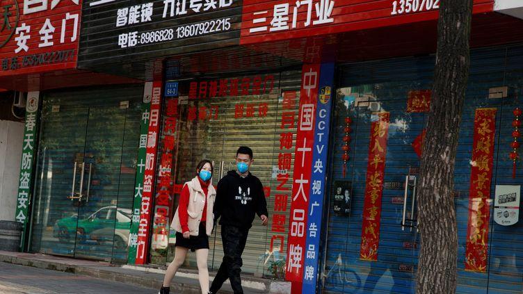Des passants marchent devant les rideaux baissés de magasins fermés à cause de l'épidémie de coronavirus, le 4 février 2020 à Jiujiang (Chine). (THOMAS PETER / REUTERS)