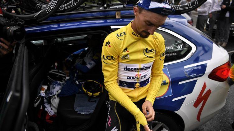 Julian Alaphilippe devant une voiture de son équipe, lors de l'arrêt de la course après une chute de grêle sur le parcours, le 26 juillet 2019 (MARCO BERTORELLO / AFP)