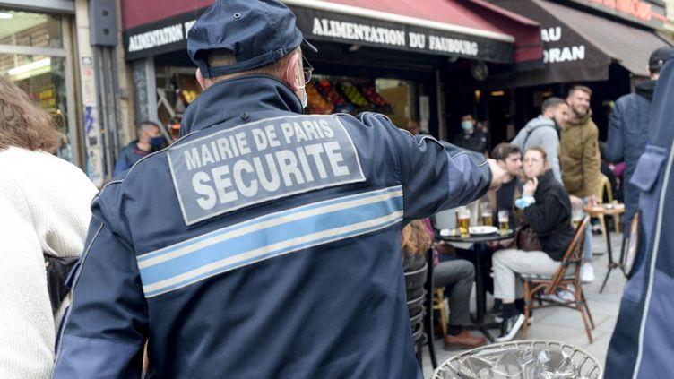 Des agents de police interviennent sur une terasse parisienne, le 19 mai 2021, pour demander aux clients de respecter les mesures sanitaires. (REMI DECOSTER / HANS LUCAS / AFP)