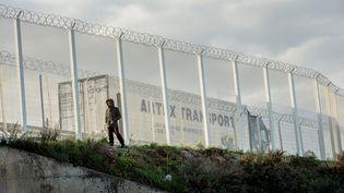 Un migrant passe devant la barrière installée par les autorités pour protéger le port des intrusions, le 25 septembre 2015, à Calais (Pas-de-Calais). (PHILIPPE HUGUEN / AFP)