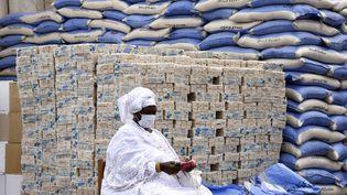 Un agent municipal préposé à la distribution de savon et de riz destinés aux habitants de Dakar, au Sénégal, attend l'arrivée des bénéficiaires, le 10 avril 2020. (SEYLLOU / AFP)