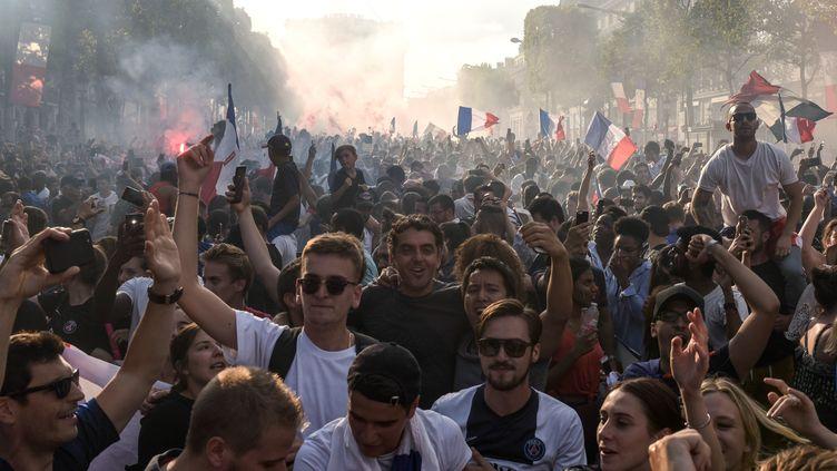 Des milliers de Français célèbrent l'arrivée des joueurs de l'équipe de France sur les Champs-Élysées à Paris, le 16 juillet. (LUCAS BARIOULET / AFP)