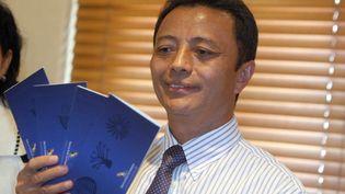L'ancien président malgache Marc Ravalomanana brandit depuis Johannesbourg (Afrique du Sud) ses billets d'avion qui l'emmèneront à Madagascar, le 21 janvier 2012. (AFP)