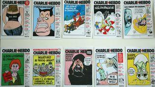 """Plusieurs couvertures de """"Charlie Hebdo"""", affichées le 15 mars 2006 dans les bureaux de l'hebdomadaire satirique à Paris. (JOEL SAGET / AFP)"""