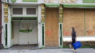 Une irlandaise passe devant un bar fermé à Dublin, le 21 octobre 2020. Depuis cette date un confinement national a été mis en place dans le pays contre la propagation du Covid-19. (PAUL FAITH / AFP)