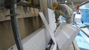 Mise en place par des ouvriers, à Auch, d'un système d'isolation thermique, avec des plaques d'isolant en polystyrène. (SEBASTIEN LAPEYRERE / MAXPPP)