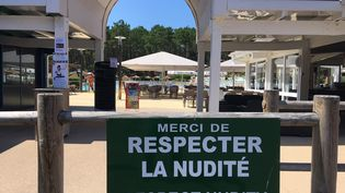 À l'entrée de la piscine du village naturiste de La Jenny en Gironde, un panneau rappelle la règle obligatoire du lieu. (EDOUARD MARGUIER / RADIO FRANCE)
