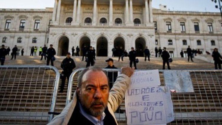 Un manifestant se tenant devant le Parlement à Lisbonne, lors d'un rassemblement contre la politique d'austérité le 21-1-2012 (AFP - PATRICIA DE MELO MOREIRA )