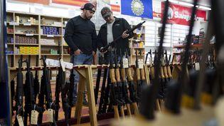 2 hommes choisissent une arme dans une armurerie à Merrimack (New Hampshire). (DOMINICK REUTER / AFP)
