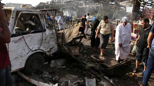 Des passants examinent les dégâts après l'explosion d'un camion piégé, le 13 août 2015 à Bagdad (Irak). (KARIM KADIM / AP / SIPA)