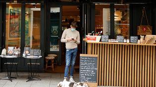L'employé d'un restaurant attend l'arrivée des clients pour la vente de repas à emporter, à Paris, le 2 novembre 2020. (LUDOVIC MARIN / AFP)